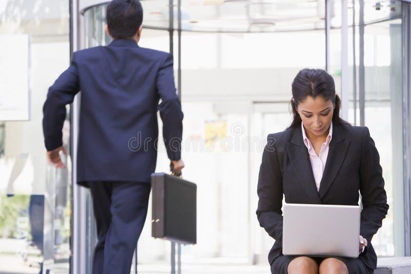 Empresaria que trabaja en la computadora portátil afuera fotografía de archivo