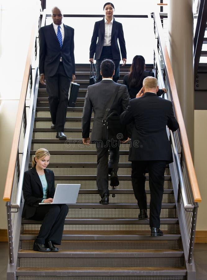 Empresaria que trabaja en la computadora portátil en la escalera de la oficina foto de archivo
