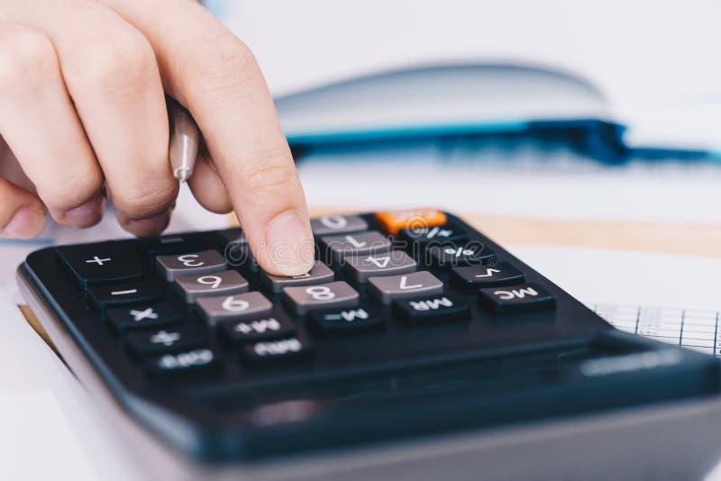 Empresaria que trabaja en la oficina con la calculadora para los datos financieros que analizan la cuenta An?lisis financiero del imágenes de archivo libres de regalías