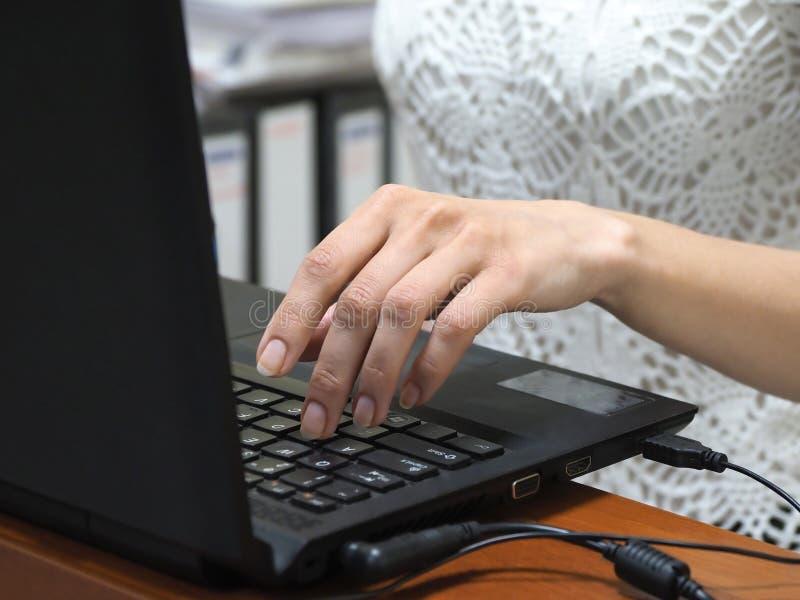 empresaria que trabaja en un ordenador port?til en la oficina Primer de la mano en el teclado fotografía de archivo