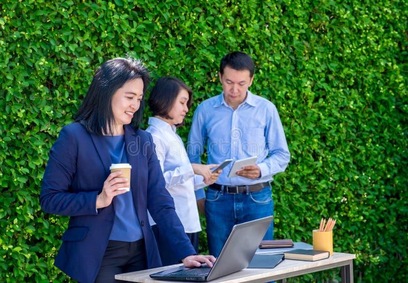Empresaria que trabaja fuera de oficina con el equipo en la hoja verde wal foto de archivo