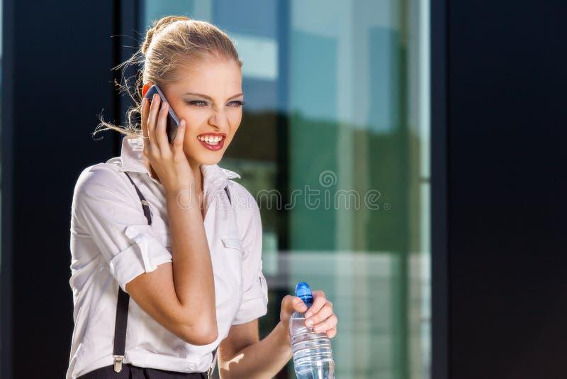 Empresaria que usa el teléfono móvil en la calle contra el edificio imagenes de archivo