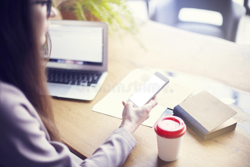 Empresaria que usa el teléfono y el ordenador portátil mientras que se sienta en su oficina moderna del desván Concepto de gente  imagen de archivo libre de regalías