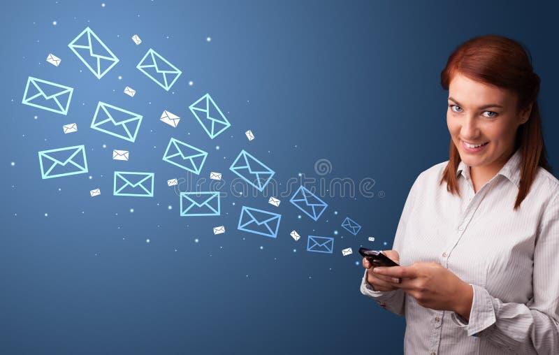 Empresaria que usa el tel?fono con concepto del correo alrededor foto de archivo