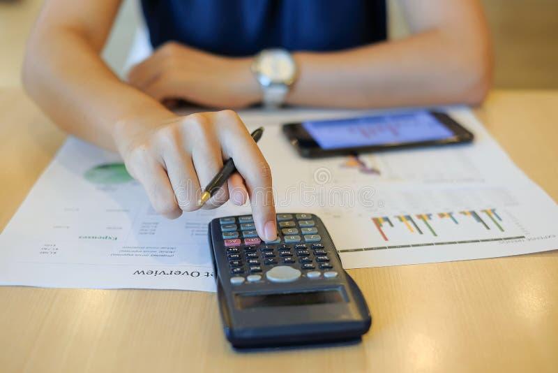 Empresaria que usa la calculadora para el plan maketing del análisis imagen de archivo
