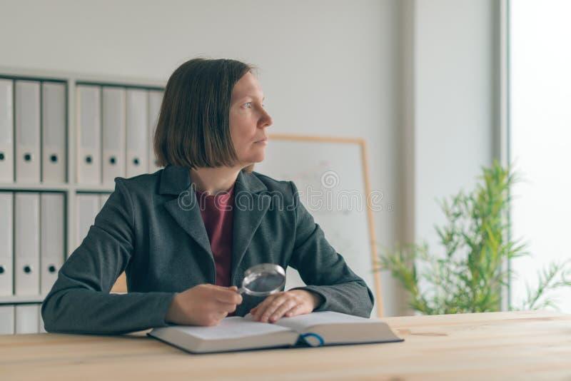 Empresaria que usa la lupa para leer el libro fotos de archivo libres de regalías