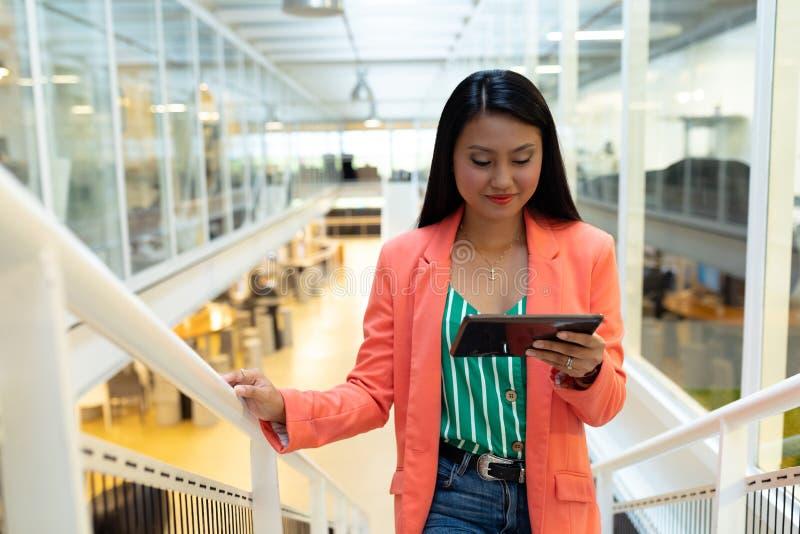 Empresaria que usa la tableta digital mientras que camina en las escaleras foto de archivo libre de regalías
