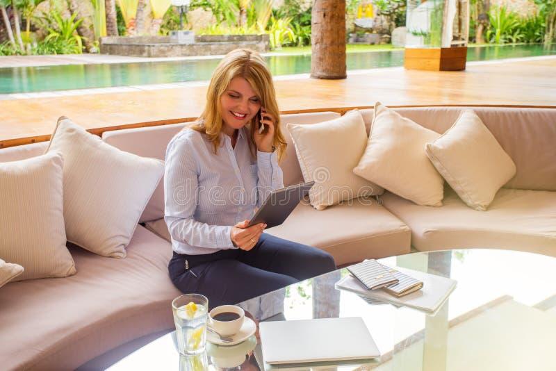 Empresaria que usa la tableta y hablando en el teléfono foto de archivo libre de regalías