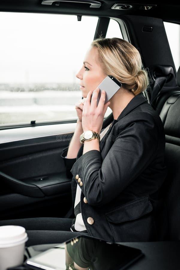 Empresaria que usa smartphone en el coche fotos de archivo