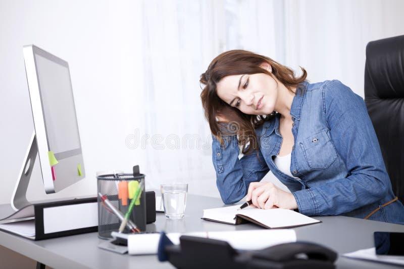 Empresaria Reading un libro con la pluma en su tabla fotografía de archivo