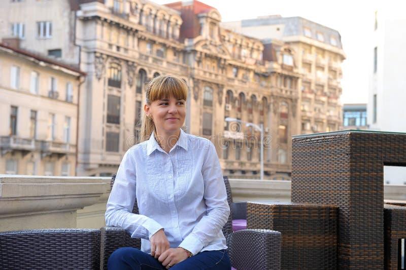 Empresaria resuelta joven que se sienta en la tabla en builin de la oficina foto de archivo libre de regalías