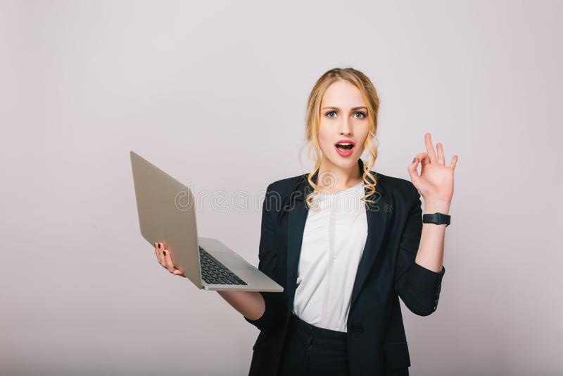 Empresaria rubia atractiva con el ordenador portátil aislado en el fondo blanco Traje de la oficina que lleva, elegante, de moda fotografía de archivo libre de regalías