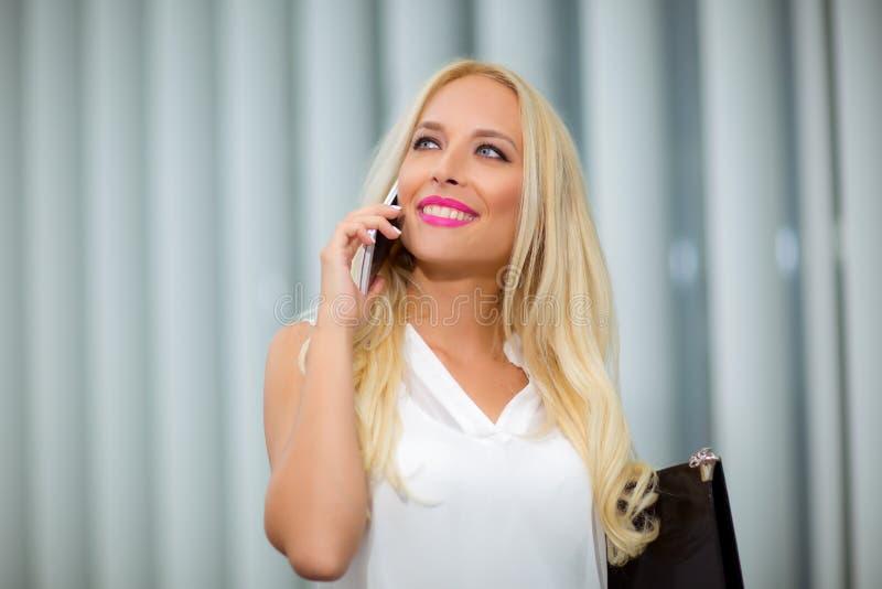 Empresaria rubia atractiva con el teléfono fotos de archivo