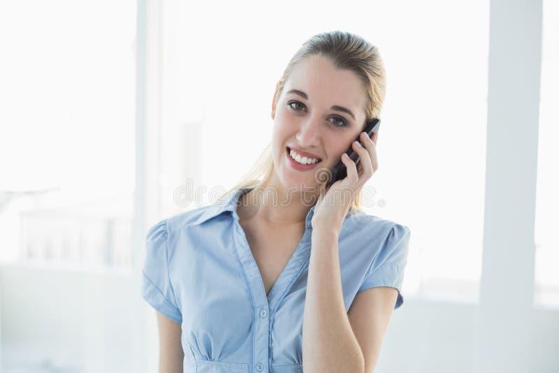 Empresaria rubia atractiva que llama por teléfono con su smartphone fotos de archivo