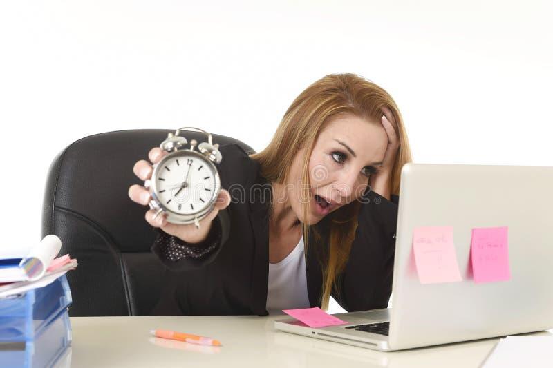 Empresaria rubia atractiva que sostiene el despertador abrumado en la tensión que trabaja con el ordenador imágenes de archivo libres de regalías