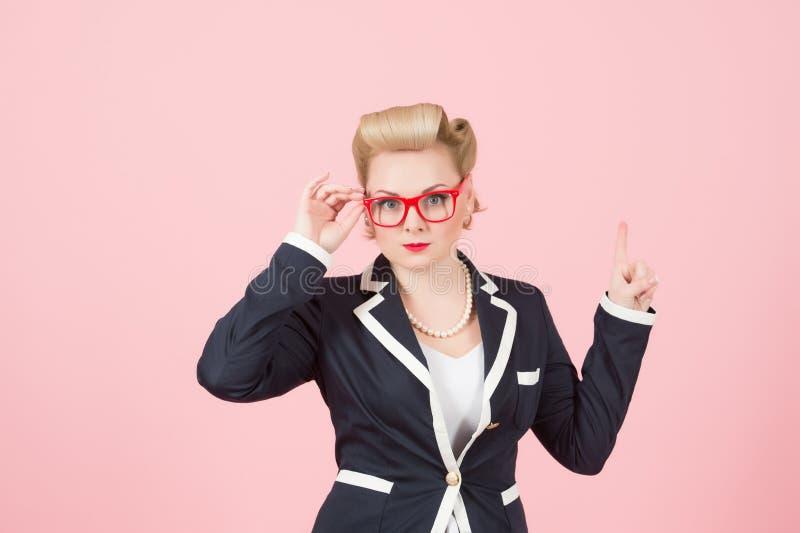 Empresaria rubia con los vidrios rojos que destaca por el finger en fondo rosado imagen de archivo