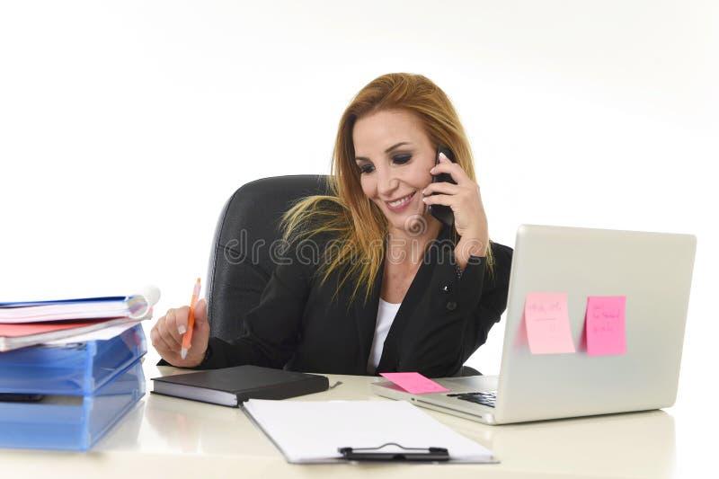 Empresaria rubia hermosa que habla en notas sonrientes de la escritura de la pluma de tenencia del teléfono móvil sobre la libret foto de archivo libre de regalías