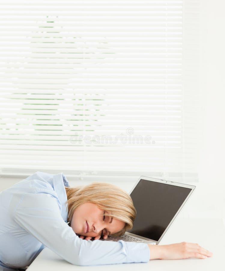 Empresaria rubia linda que duerme en su cuaderno imagenes de archivo