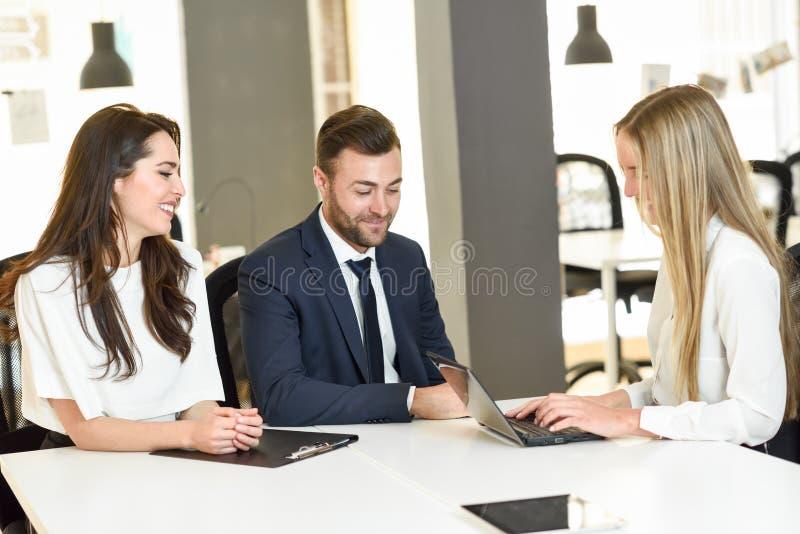 Empresaria rubia que explica con el ordenador portátil al cou joven sonriente fotografía de archivo libre de regalías