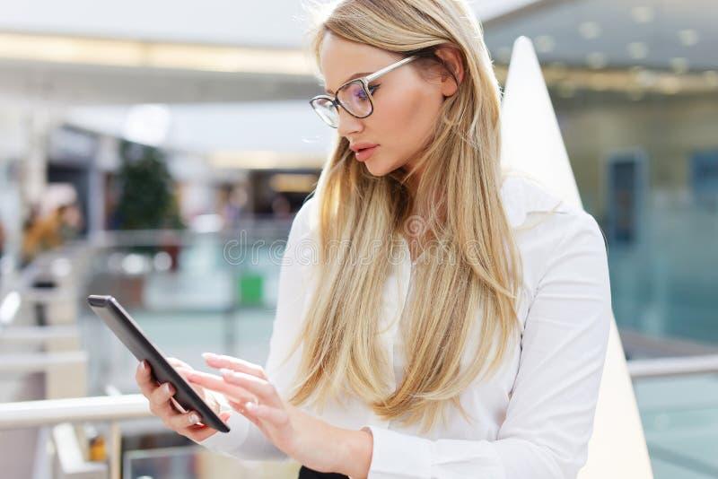 Empresaria rubia que usa la tableta en centro de negocios fotos de archivo
