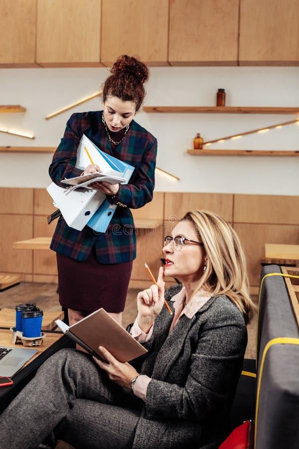 empresaria Rubio-cabelluda que da tareas a la secretaria útil joven foto de archivo libre de regalías