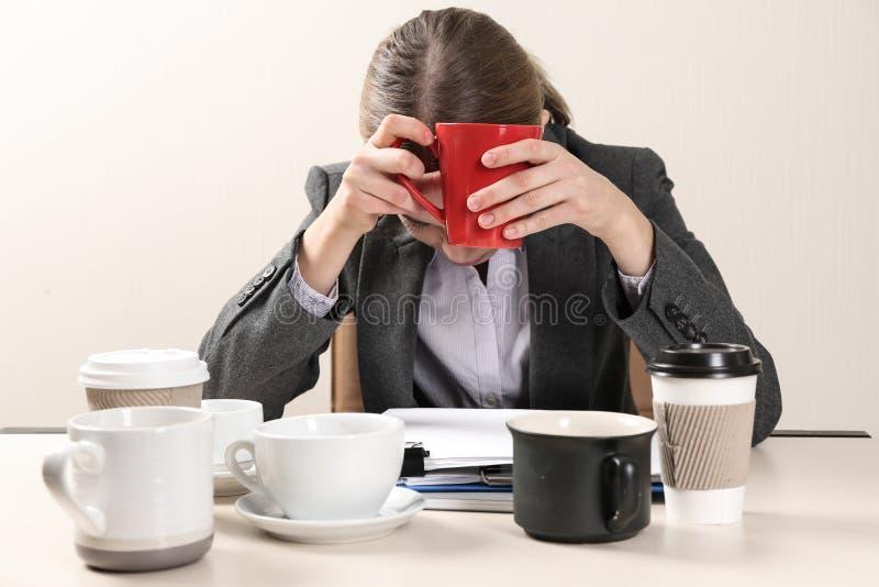 Empresaria soñolienta con muchas tazas de café vacías que se sientan en la tabla en oficina Concepto de apego foto de archivo libre de regalías
