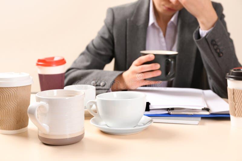 Empresaria soñolienta con muchas tazas de café vacías que se sientan en la tabla en oficina Concepto de apego imagen de archivo