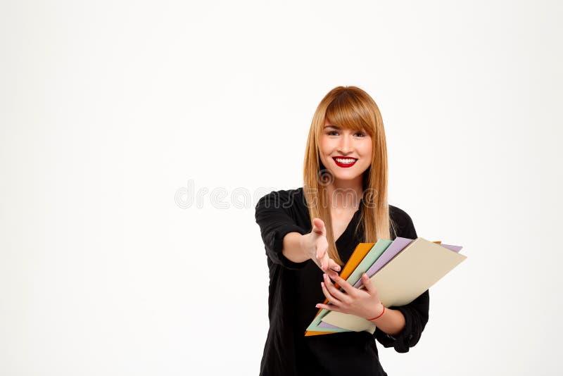 Empresaria sonriente acertada que sostiene carpetas sobre el fondo blanco Copie el espacio fotografía de archivo