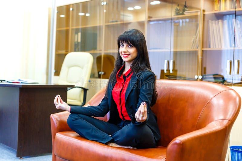 Empresaria sonriente bonita que se sienta en el sofá en el posi del loto fotografía de archivo