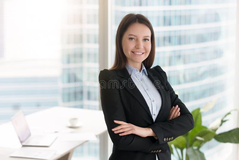 Empresaria sonriente confiada joven que se coloca en oficina con AR fotografía de archivo libre de regalías