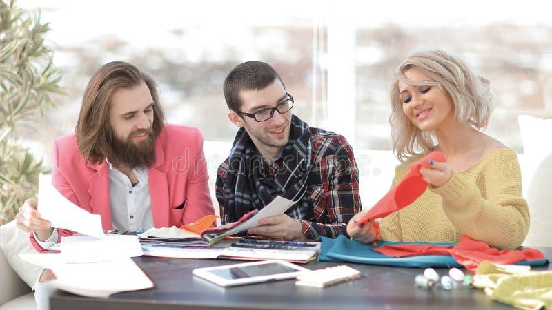 Empresaria sonriente del sastre que se sienta en la máquina de coser y la fabricación de la ropa hecha a mano mientras que comerc fotos de archivo libres de regalías