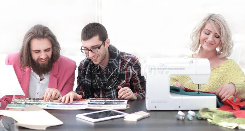 Empresaria sonriente del sastre que se sienta en la máquina de coser y la fabricación de la ropa hecha a mano mientras que comerc foto de archivo