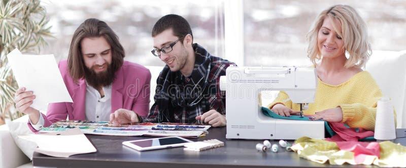 Empresaria sonriente del sastre que se sienta en la m?quina de coser y la fabricaci?n de la ropa hecha a mano mientras que comerc imagen de archivo libre de regalías