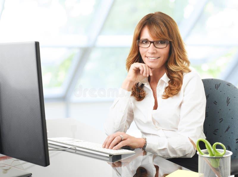 Empresaria sonriente en el escritorio de oficina con un ordenador fotografía de archivo