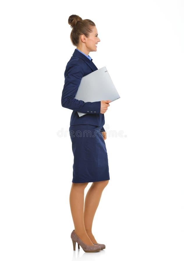 Empresaria sonriente en el traje que se coloca en fichero de tenencia del perfil fotos de archivo libres de regalías