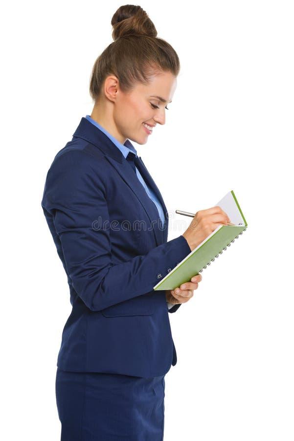Empresaria sonriente en la situación del perfil, escritura en cuaderno foto de archivo
