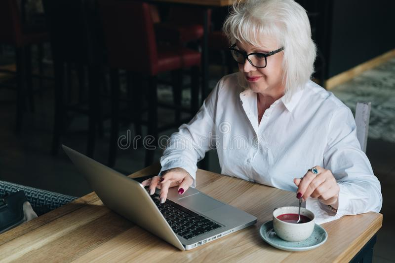 Empresaria sonriente en los vidrios que se sientan en la tabla, trabajando en el la fotos de archivo