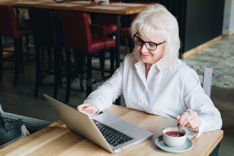 Empresaria sonriente en los vidrios que se sientan en la tabla, trabajando en el la foto de archivo libre de regalías