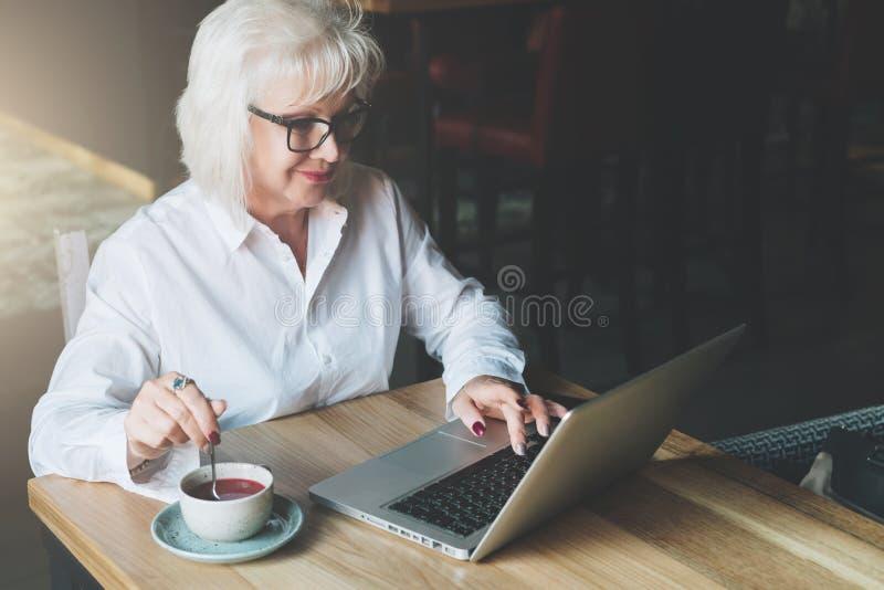 Empresaria sonriente en los vidrios que se sientan en la tabla, trabajando en el la fotos de archivo libres de regalías