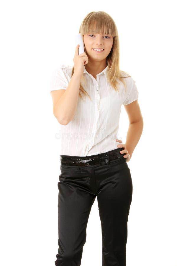 Empresaria sonriente feliz en el teléfono en la oficina foto de archivo libre de regalías