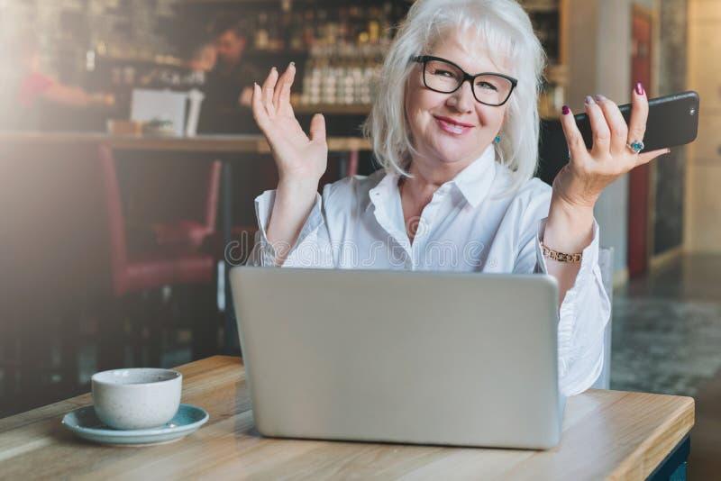 Empresaria sonriente feliz que se sienta en la tabla delante del ordenador portátil, levantando las manos, trabajo, aprendiendo imagen de archivo libre de regalías