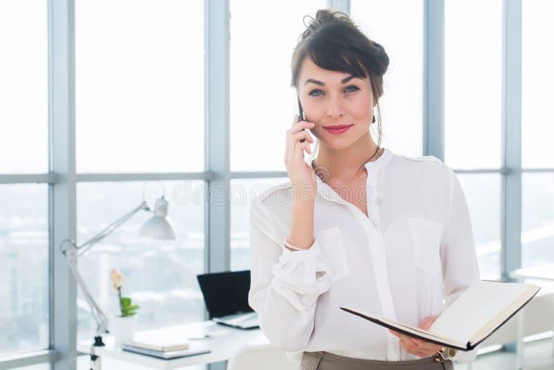 Empresaria sonriente feliz que tiene una llamada del negocio, discutiendo las reuniones, planeando su día del trabajo, usando sma fotografía de archivo libre de regalías