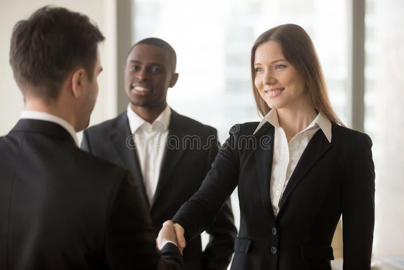 Empresaria sonriente hermosa y apretón de manos del hombre de negocios, abeto foto de archivo libre de regalías