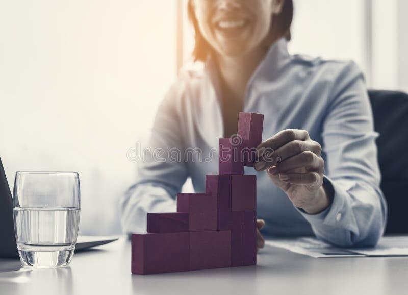 Empresaria sonriente que construye una carta financiera acertada imagenes de archivo