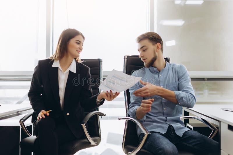Empresaria sonriente que da los papeles alguien en oficina imagen de archivo