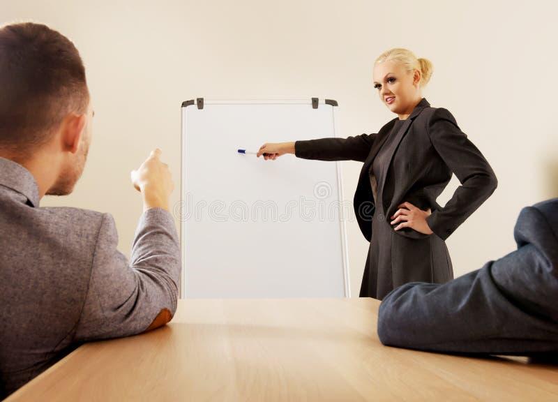 Empresaria sonriente que dibuja un gráfico para sus colegas en el whiteboard foto de archivo libre de regalías