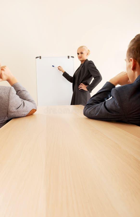 Empresaria sonriente que dibuja un gráfico para sus colegas en el whiteboard fotos de archivo libres de regalías
