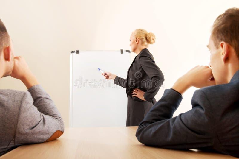 Empresaria sonriente que dibuja un gráfico para sus colegas en el whiteboard fotos de archivo