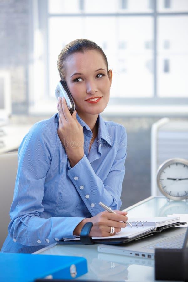 Empresaria sonriente que habla en el teléfono móvil imagenes de archivo