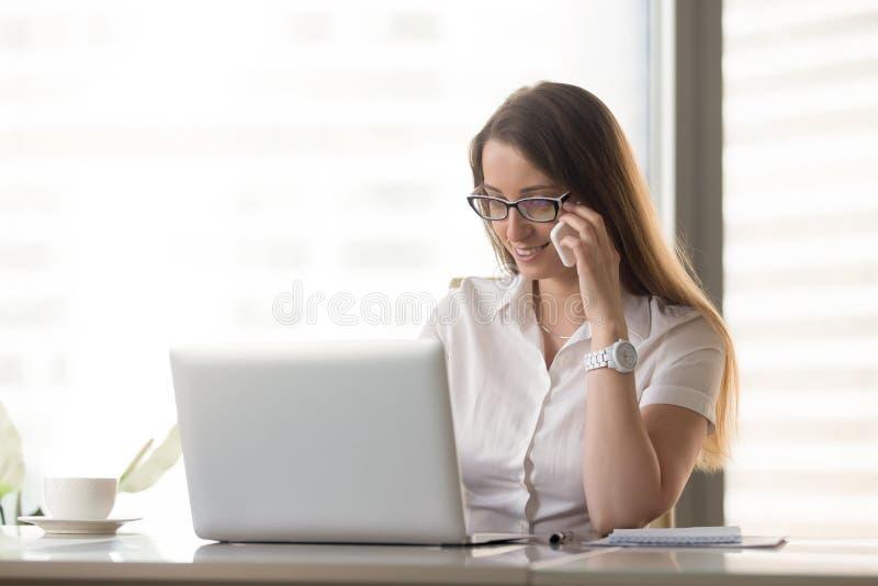 Empresaria sonriente que habla en el teléfono mientras que usa el ordenador portátil, calli foto de archivo libre de regalías
